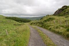 Grintweg door groene heuvels stock afbeeldingen