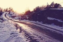 Grintweg tussen rotsen met ijs worden behandeld dat Stock Afbeeldingen