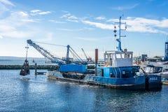 Grip H-hornet för Dredger C på arbete som muddrar den Poole hamnmarina i Dorset, UK royaltyfri foto