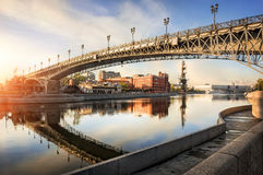 In the grip of steel. Arch of the Patriarchal bridge with reflection in the water and the monument to Peter the Great in the distance royalty free stock image