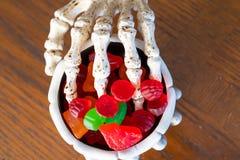 Gripande bunke för skelett- hand av godisen under halloween arkivfoton