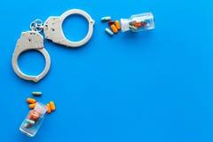 Gripande för olagligt köp-, besittning- och försäljningsdrogbegrepp Droger som piller nära handbojan på bästa sikt för blå bakgru arkivbild