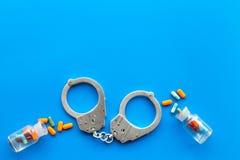 Gripande för olagligt köp-, besittning- och försäljningsdrogbegrepp Droger som piller nära handbojan på bästa sikt för blå bakgru royaltyfri bild