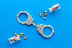 Gripande för olagligt köp-, besittning- och försäljningsdrogbegrepp Droger som piller nära handbojan på bästa sikt för blå bakgru royaltyfri foto