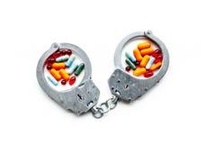 Gripande för olagligt köp-, besittning- och försäljningsdrogbegrepp Droger som piller nära handbojan på den vita bakgrundsöverkan arkivfoto