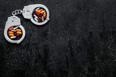 Gripande för olagligt köp-, besittning- och försäljningsdrogbegrepp Droger som piller nära handbojan på svart bakgrundsöverkant royaltyfria bilder