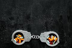 Gripande för olagligt köp-, besittning- och försäljningsdrogbegrepp Droger som piller nära handbojan på svart bakgrundsöverkant arkivbild
