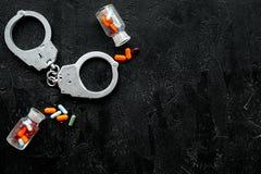 Gripande för olagligt köp-, besittning- och försäljningsdrogbegrepp Droger som piller nära handbojan på svart bakgrundsöverkant royaltyfri bild