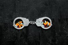 Gripande för olagligt köp-, besittning- och försäljningsdrogbegrepp Droger som piller nära handbojan på svart bakgrundsöverkant royaltyfri fotografi