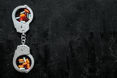 Gripande för olagligt köp-, besittning- och försäljningsdrogbegrepp Droger som piller nära handbojan på svart bakgrundsöverkant arkivfoton