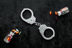 Gripande för olagligt köp-, besittning- och försäljningsdrogbegrepp Droger som piller nära handbojan på svart bakgrundsöverkant arkivfoto