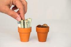 Gripande pengar för hand i en terrakottakruka Arkivfoton