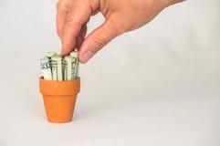 Gripande pengar för hand i en terrakottakruka Fotografering för Bildbyråer