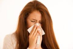 Gripe de la enfermedad - mujer joven que miente en la cama infectada con la alergia Blo foto de archivo