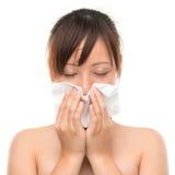Gripe ou frio - espirrando o nariz de sopro doente da mulher. Imagem de Stock