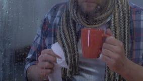 Gripe sufridora masculina de mediana edad, té de consumición y estornudo, vacunación de la gripe almacen de video