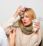 Gripe y tratamiento frío Muchacha en la bufanda examinada por el doctor Remedios de la fiebre y de la gripe Mujer consultar con e fotografía de archivo