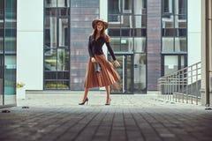Griper den eleganta kvinnan för lyckligt mode som bär ett svart omslag, den bruna hatten och kjolen med en handväska att gå på eu royaltyfri foto