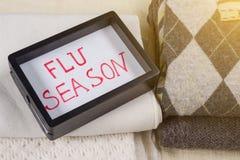 Grippe-Saison - Text im Rahmen Warme woolen Kleidung des Hintergrundes Lizenzfreies Stockfoto
