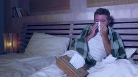Grippe sufridor del dormitorio del hombre joven en casa que siente nariz de estornudo y que sopla mal y enferma cubierta con la m almacen de metraje de vídeo