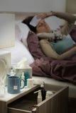 Grippemedizin auf Nachttisch-Krankefrau Stockbild