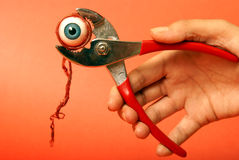 Gripping Horror. An eyeball feels the squeeze of a pair of pliers Royalty Free Stock Photography