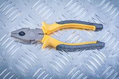 Gripping tongs on fluted metal background construction concept Royalty Free Stock Photography