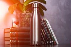 Gris de bouteille thermo de couleur au-dessus du fond des livres et de la fleur verte Avec l'effet de lumière du soleil photos stock