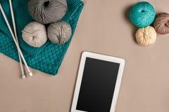 Gris et laine de tricotage de turquoise, aiguilles de tricotage et un comprimé avec un écran noir sur le fond beige Vue supérieur Photos stock