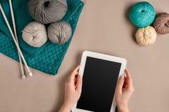 Gris et laine de tricotage de turquoise, aiguilles de tricotage et un comprimé avec un écran noir sur le fond beige Vue supérieur Image stock