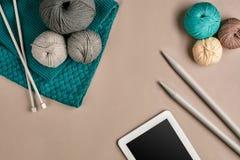 Gris et laine de tricotage de turquoise, aiguilles de tricotage et un comprimé avec un écran noir sur le fond beige Vue supérieur Photos libres de droits