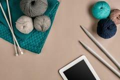 Gris et laine de tricotage de turquoise, aiguilles de tricotage et un comprimé avec un écran noir sur le fond beige Vue supérieur Images libres de droits