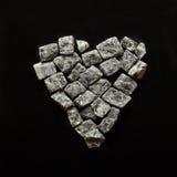 Gris machacado hermoso en un fondo negro, corazón de piedra del granito Foto de archivo