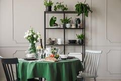 Gris y sillas de madera negras en la mesa redonda con el mantel, las placas, las tazas y las copas de vino verdes foto de archivo libre de regalías