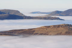 Grisedale Pike from Helvellyn. High on the Lakeland tops looking across a temperature inversion that blankets the dales and valleys below Royalty Free Stock Image