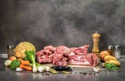 Griskött, grönsak och krydda på köksbordet fotografering för bildbyråer