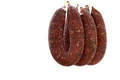 Griskött- och nötköttkorvar som hängs på krokar och att vänta för att få torrt Arkivfoton