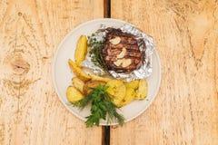 Grisköttbiff i folie med potatisar royaltyfri foto