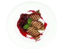 Grisköttbiff med körsbärsröd sås Arkivbild