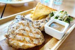 Grisköttbiff med vitlökbröd och BBQ-sås Arkivfoto