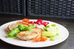 Grisköttbiffar med grönsaker på den vita plattan på mörk bakgrund royaltyfria foton