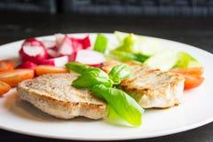 Grisköttbiffar med grönsaker på den vita plattan på mörk bakgrund arkivfoton