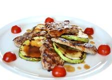 Grisköttfläskkarré med englace sås, en zucchini och körsbärsröda tomater Royaltyfri Bild