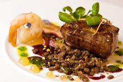 Grisköttkött med räkan på den vita plattan Arkivbilder