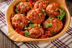 Grisköttköttbullar med kryddig tomatsås i maträtt Arkivfoton