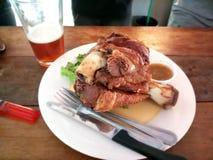 Grisköttknoge eller djupt stekt grisköttben med hantverköl royaltyfri foto