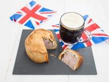 Grisköttpaj och öl med flaggor Arkivfoto