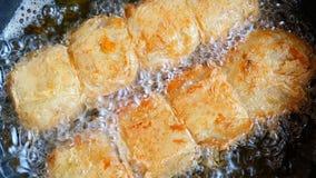Grisköttrulle som steker i panna på köket det är sjuklig mat som innehåller många av kolesterol och fett arkivfilmer