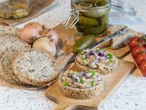 Grisköttspridning, späcker och sura gurkor på nytt runt bröd som strilas med våren och den röda löken Royaltyfria Foton