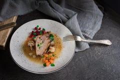 Grisköttstöd med beta, morötter, stekte champinjoner och sås på en vit platta Restaurangportion Gammal svart lantlig bakgrund öve royaltyfria foton